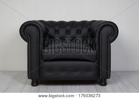 Black leather armchair on white wooden floor near white textured wall