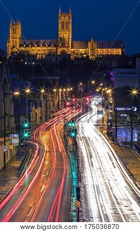 LINCOLN UK - FEBRUARY 2017: A view of Lincoln Cathedral overlooking light trails from traffic in the historic city of Lincoln in the UK on 27th February 2017.