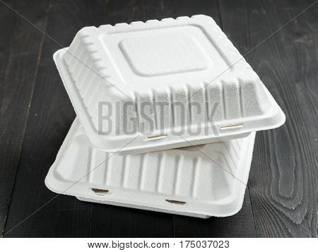 Two closed disposable take out container. Gray closed cardboard lunch box on dark wooden background