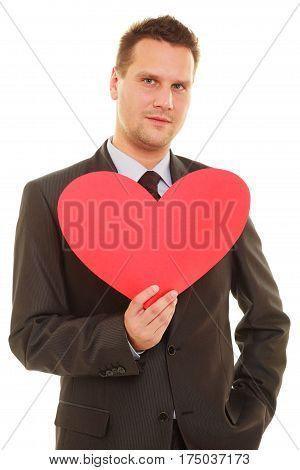 Adult flirting guy in elegant suit holding heart made of paper love symbol