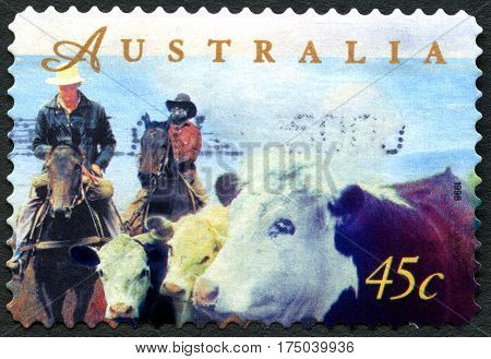 AUSTRALIA - CIRCA 1998: A used postage stamp from Australia depicting an illustration of farmers herding cattle on horseback circa 1998.