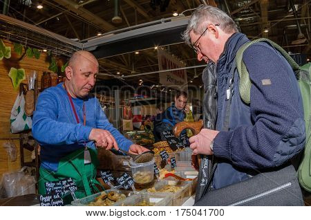 Moscow, Russia - February 25, 2017: Seller of home produced pickled mushrooms at the fair fills a jar for the buyer