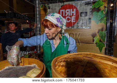 Moscow, Russia - February 25, 2017: Red-haired woman prepares national Korean fast food pyan-se in a traditional bamboo steamer