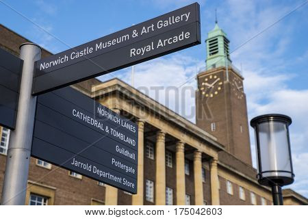 Directional sign in the historic city of Norwich pointing towards the many landmarks and places of interest within the city. The City Hall of Norwich is in the background.