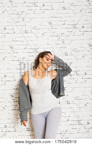 Beautiful tired fit young brunette woman standing against white brick wall, wearing sporty clothes in gray, wiping her forehead from sweat. Mild retouch, copy space, studio lighting.