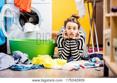 Tired housewife lying on the floor with lots of clothes near the washing machine at home