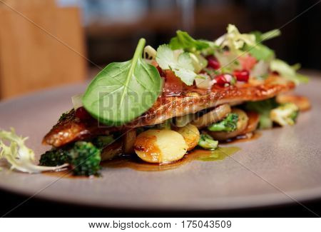 Fish fillet with vegetables, potatoes and herbs, fusion cuisine dish