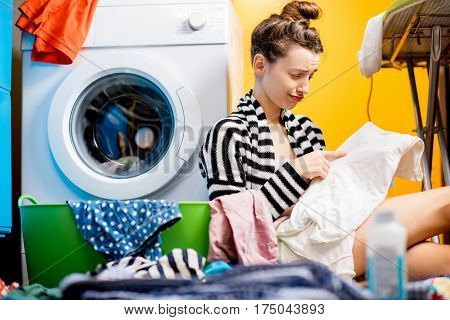Upset housewife looking on the dirty clothes sitting near the washing machine at home