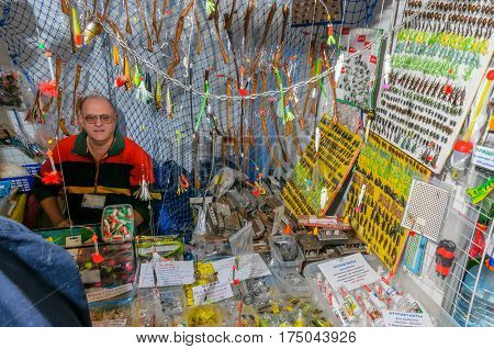 Moscow, Russia - February 25, 2017: An elderly seller of fishing-baits behind a counter with wobblers and artifical insects for flyfishing