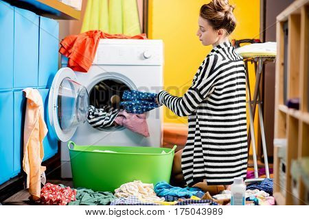 Young housewife loading clothes into the washing machine sitting on the floor at home