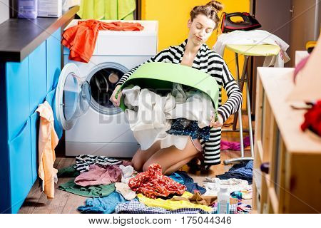 Young housewife sitting with clothes basket near the washing machine at home