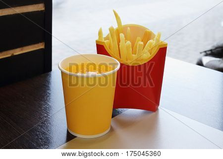 Carbonated drink and French fries on the table in a cafe