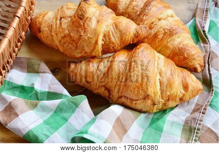 Corissants in the basket on wooden background.
