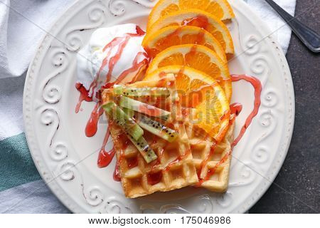 Tasty waffles with delicious fruits, ice-cream and syrup on white plate