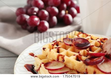 Tasty waffles with delicious grape, ice-cream and syrup on white plate, close up