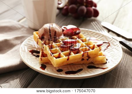 Tasty waffles with delicious grape, ice-cream and syrup on white plate