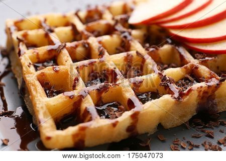Delicious waffle with apple slices, syrup and chocolate shavings on plate, close up