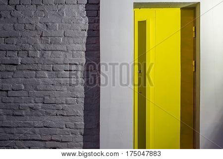 Dark gray brick wall with a design yellow door. Light shines on the door from the right. Outdoors. Closeup. Horizontal.