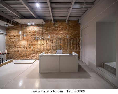Luminous office in a loft style with brick and gray walls. There are many different hanging lamps. Also there is a gray reception desk with a laptop and chair, metal table with a stool. Horizontal.