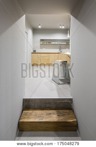 Entrance with a wooden doorstep to the kitchen in a loft style with gray walls. There is light wooden lockers and tabletop with a sink shelves with cups, design stool, glowing lamps. Vertical.