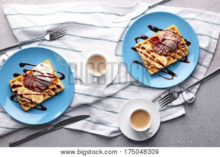 Tasty waffles with delicious fruits, ice-cream and syrup on blue plates