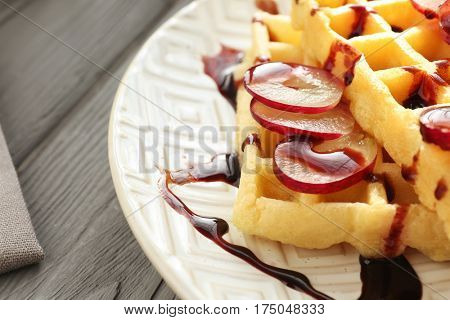 Tasty waffles with delicious grape and syrup on white plate, close up
