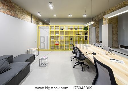 Office in loft style with gray and brick walls. There are glowing lamps, dark sofa with pillow, wooden tables with chairs, small metal tables, metal yellow shelves with accessories, door. Horizontal.