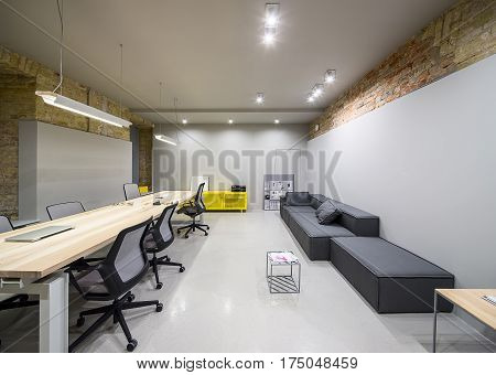 Modern office in a loft style with gray and brick walls. There are glowing lamps, wooden tables with chairs, metal yellow lockers, dark sofas with pillows, small metal table. Horizontal.