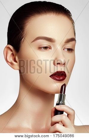 Fashion And Beauty. Beautiful Young Woman With Wine Lipstick