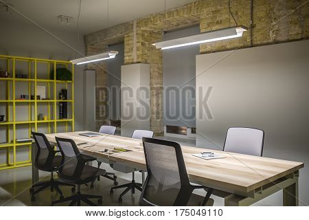 Loft style workplace with gray and brick walls. There are glowing lamps over the wooden tables with black-gray chairs, metal yellow shelves, windows with dark gray curtains. Horizontal.