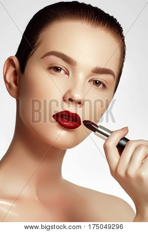 Cosmetics And Makeup. Perfect Lip Makeup. Fashion Model Applying Lipstick. Beautiful Young Woman Wit