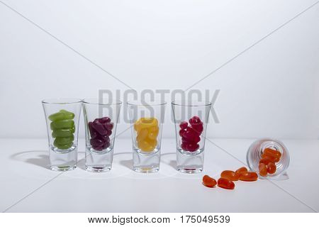 Multi coloured jelly beans in small clear glasses on a white background.