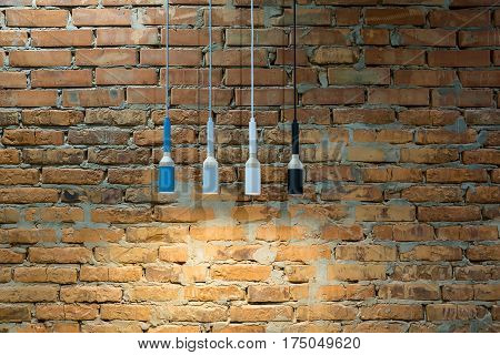 Luminous hanging multi-colored lamps in a loft style on the brick wall background. Closeup. Horizontal.