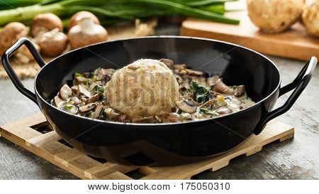 Homemade bavarian bread dumpling with creamed mushrooms and herbs.