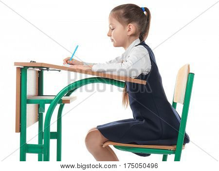 Incorrect posture concept. Little girl sitting at school desk on white background