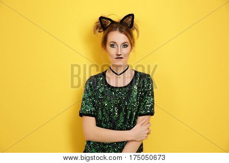 Beautiful young woman with cat makeup and ears on color background