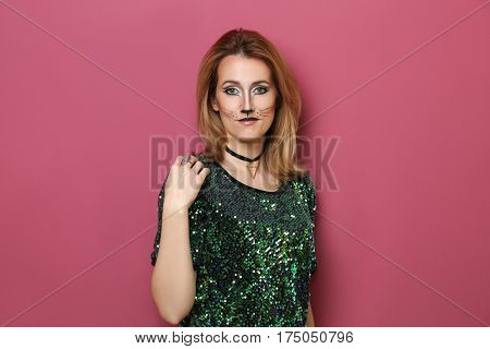 Beautiful young woman with cat makeup on color background