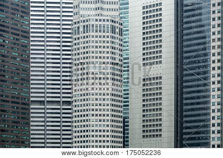 Modern cityscape of several close standing skyscrapers in Singapore. Central skyscraper has a polygon form. Horizontal.