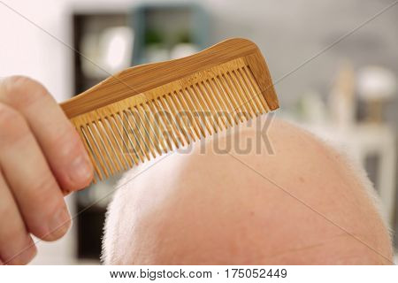 Senior bald man with comb on blurred background, closeup
