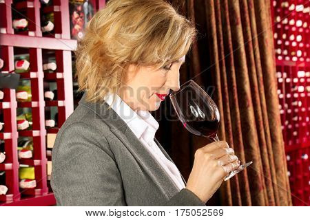 Cheerful woman with glass of red wine in modern cellar