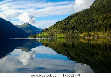 gudvangen fjord in norway refleting on the water on a blue sky with clouds background