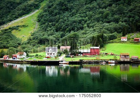 colored wooden houses in norway reflecting on the water