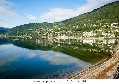 norway small town reflecting on the water blue sky background