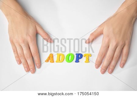 Female hands and word ADOPT on white background