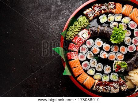 Japanese Cuisine. Sushi Set In A Round Plate Over Dark Concrete Background.