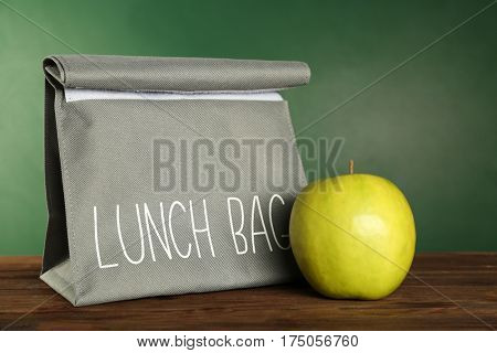 Grey lunch bag and appetizing green apple on wooden table against blackboard background