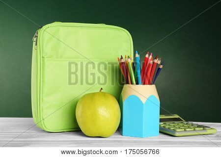 Holder with colorful pencils, lunch bag and appetizing green apple on wooden table against blackboard background