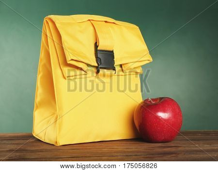 Yellow lunch bag and appetizing red apple on wooden table against blackboard background