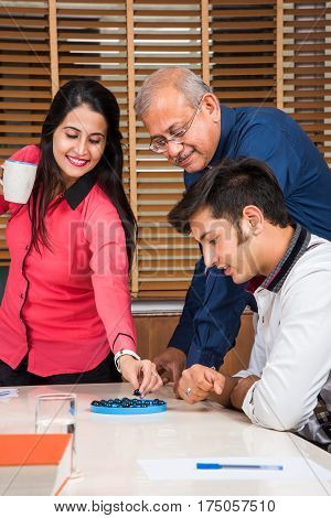 Indian senior  businessman or boss playing brainvita game with employee in the office in playful atmosphere, selective focus