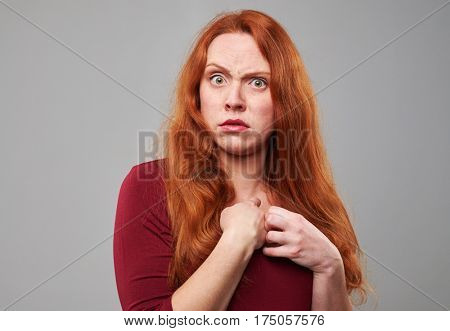 Close-up studio portrait of disaffected woman with red hair. Showing negative emotions. Isolated over background